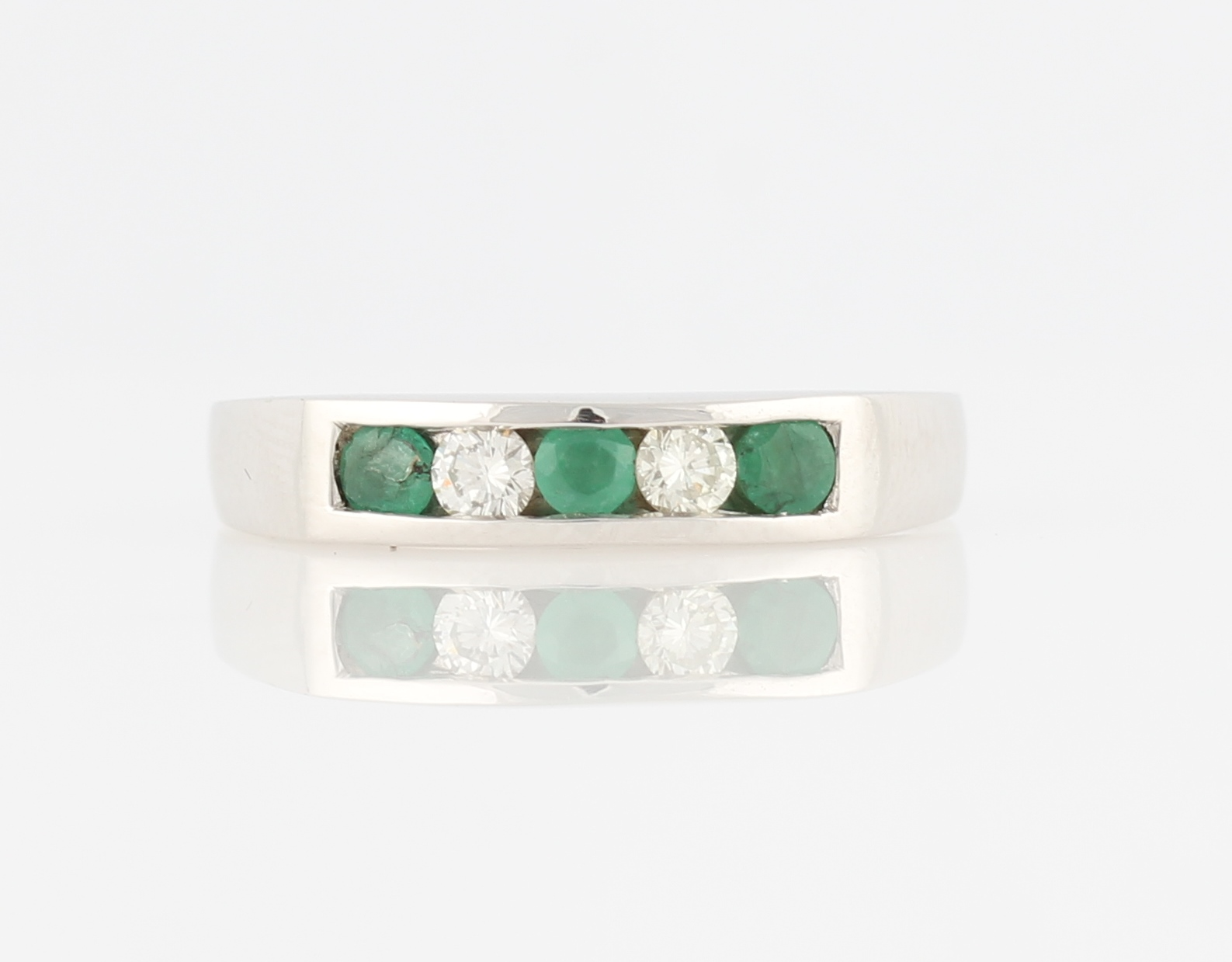 Lot 35 - A hallmarked 18ct white gold emerald and diamond half eternity ring, set alternately with three