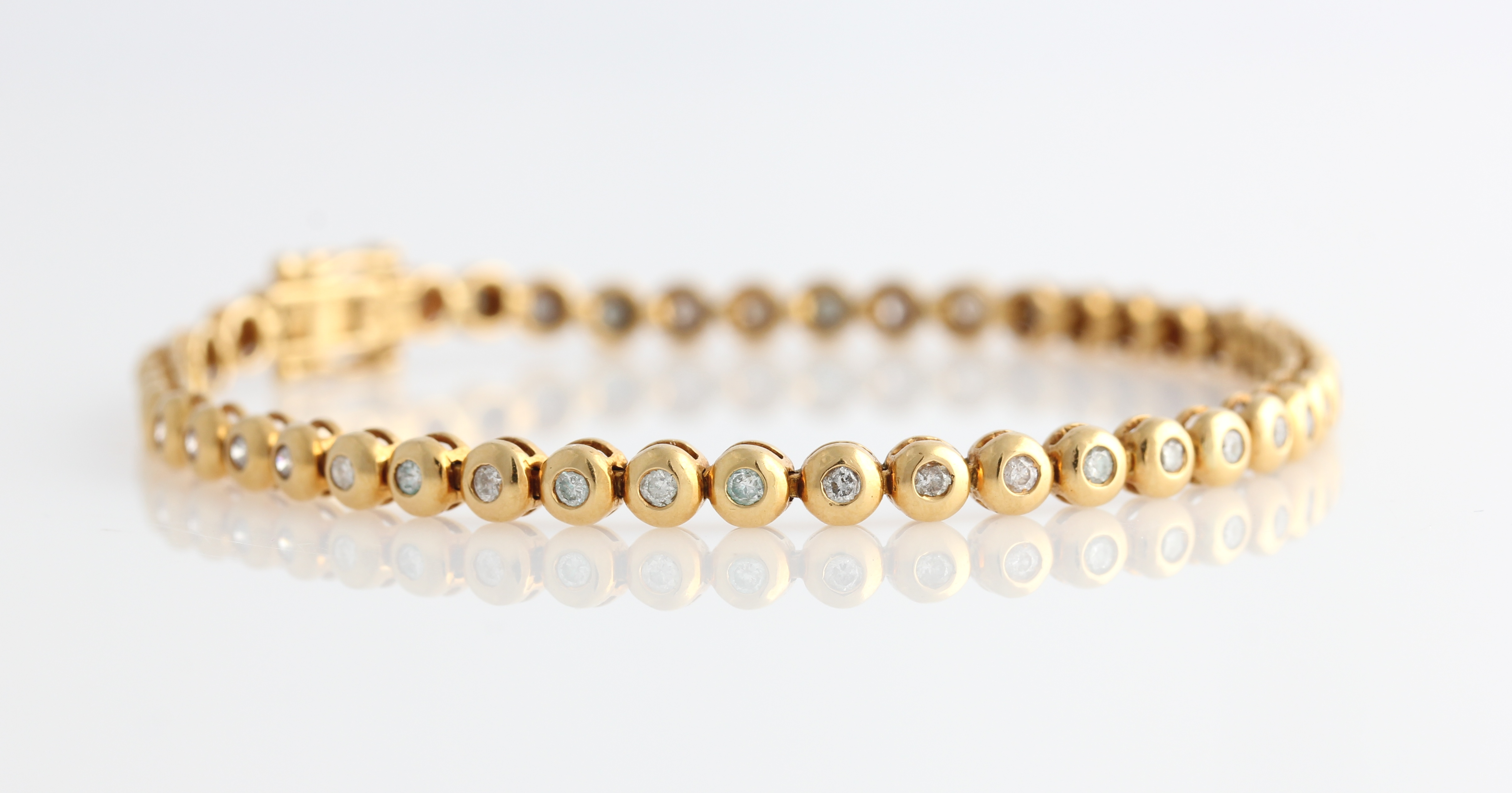 Lot 50 - A hallmarked 18ct yellow gold diamond tennis bracelet, each articulated circular link set with a