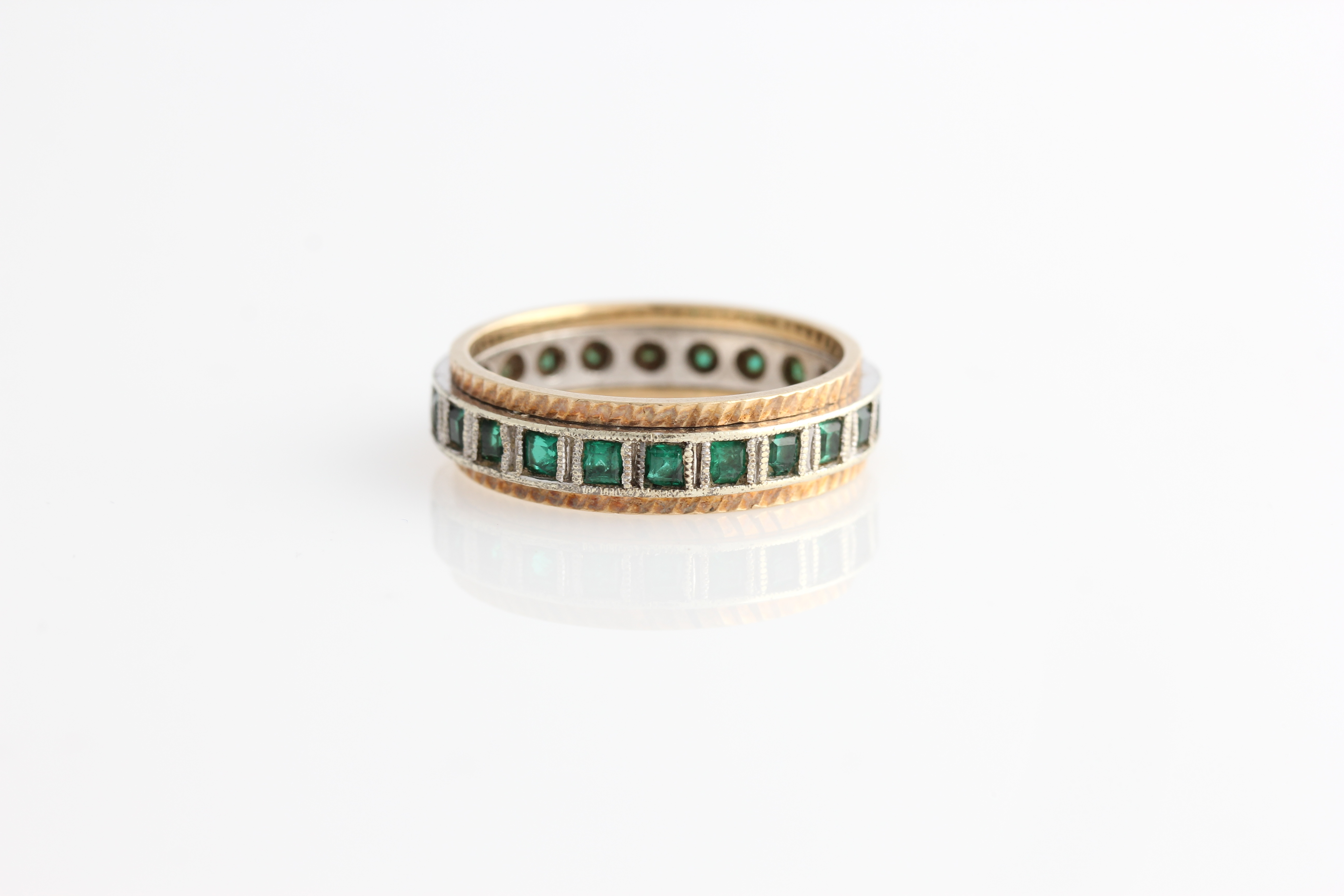 Lot 60 - A green stone full eternity ring, hallmark indistinct, ring size O½.