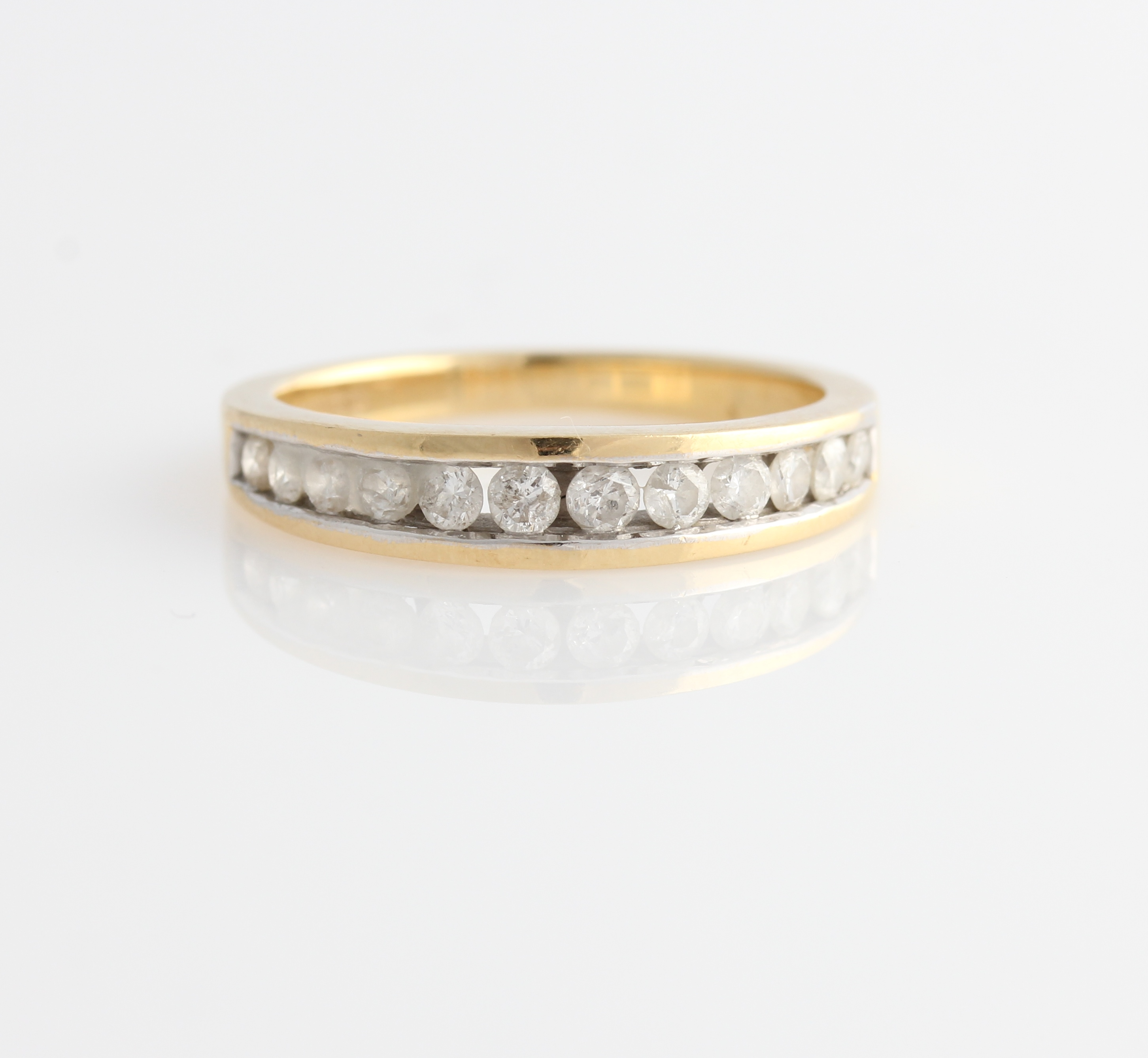Lot 49 - A hallmarked 18ct yellow gold diamond half eternity ring, channel set with twelve graduated round