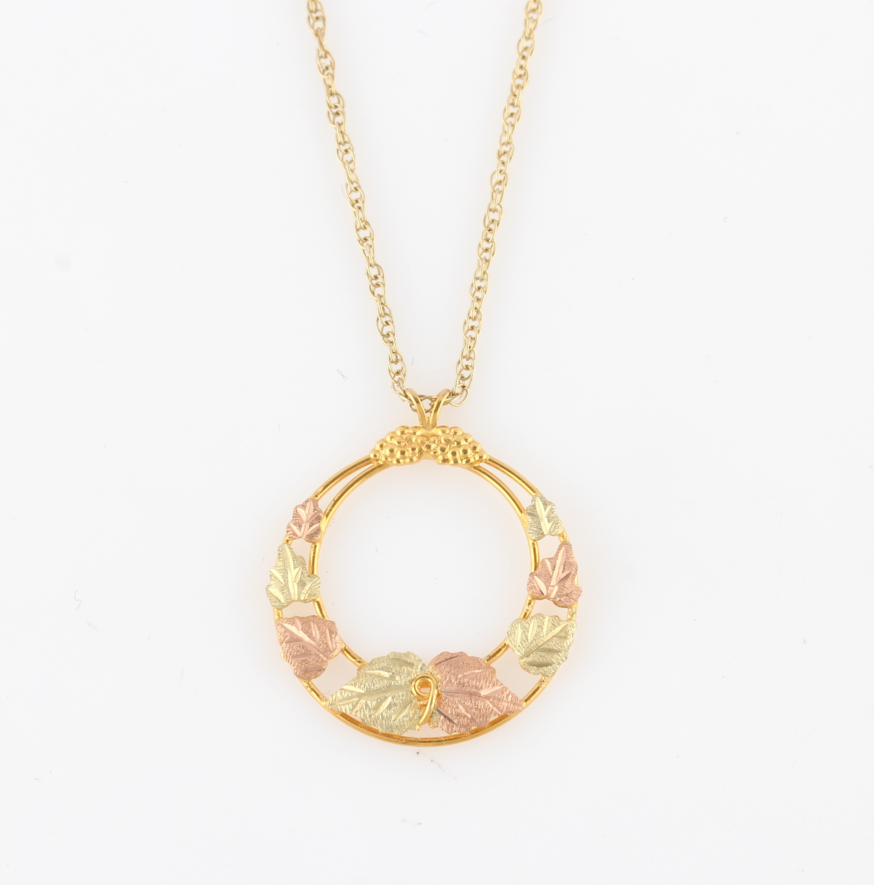 Lot 10 - A 9ct two-tone gold pendant, of circular open metalwork design featuring leaves, hallmarked London