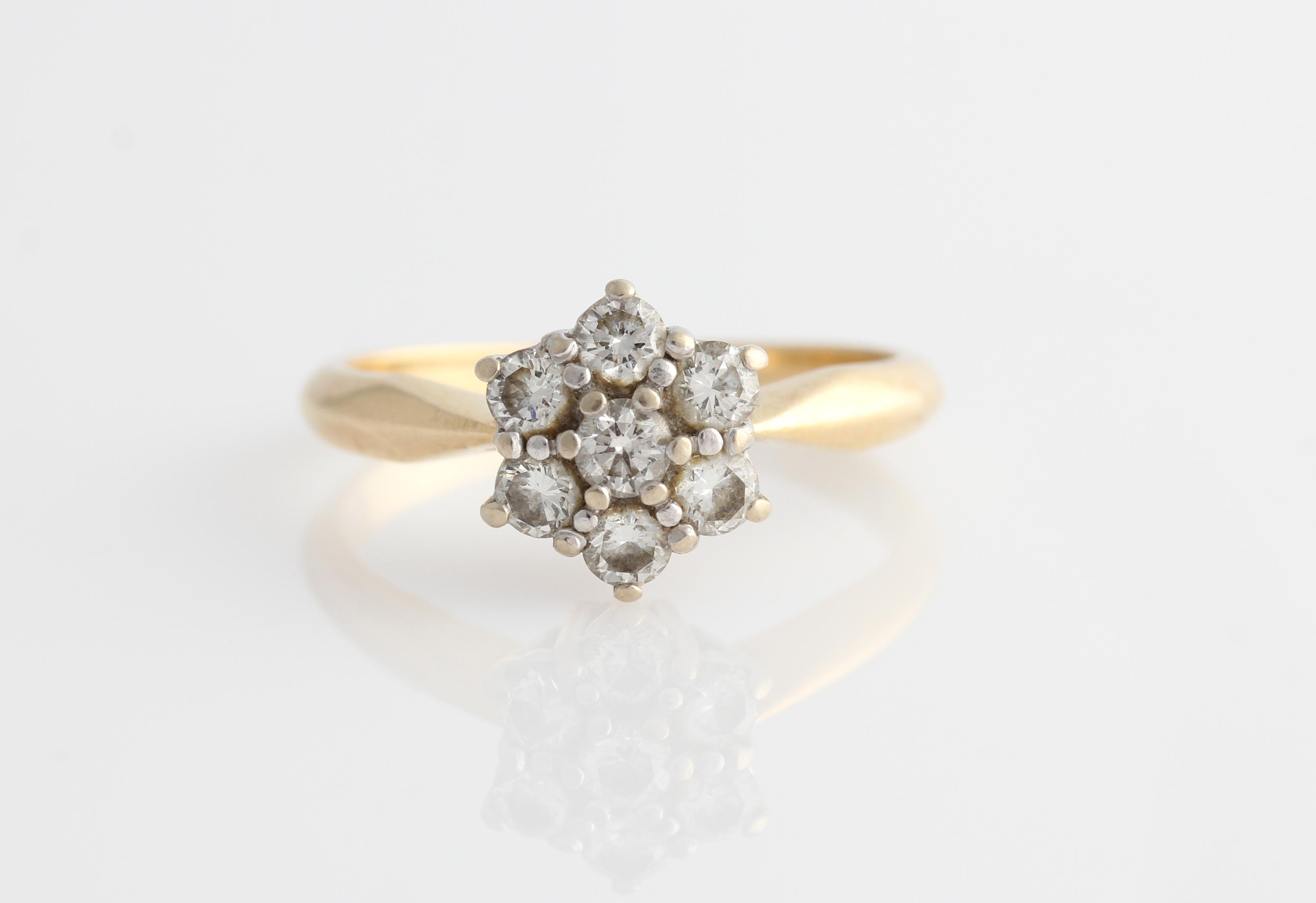 Lot 53 - A diamond flower design ring, set with seven round brilliant cut diamonds, total diamond weight