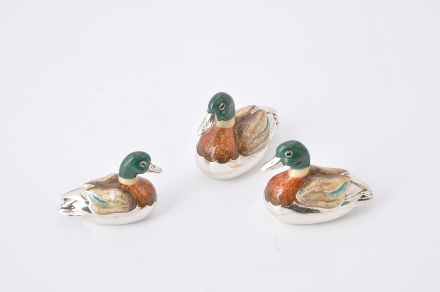 A graduated set of three silver and enamel model ducks by J A H