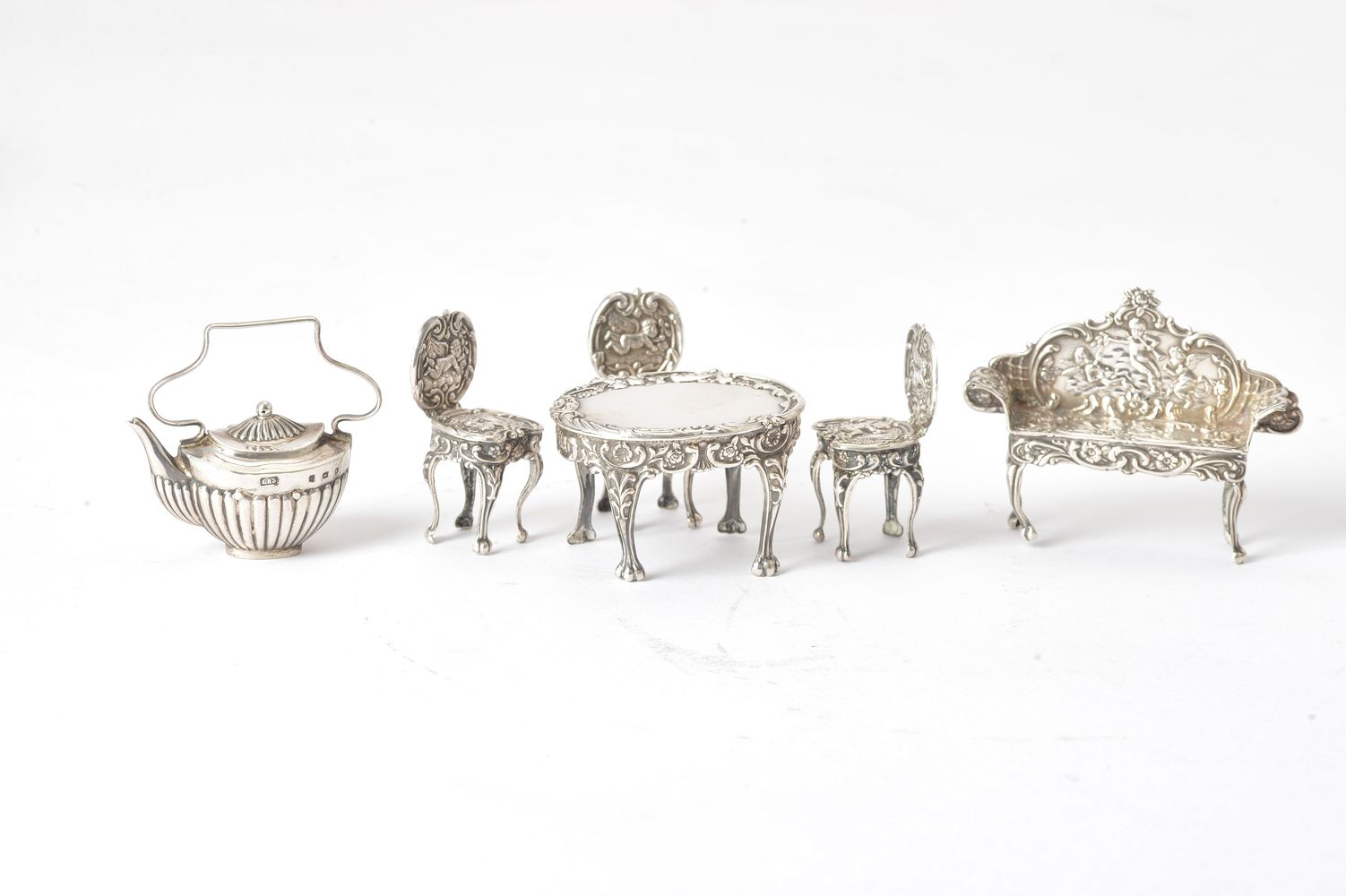 A collection of silver toys mainly furniture