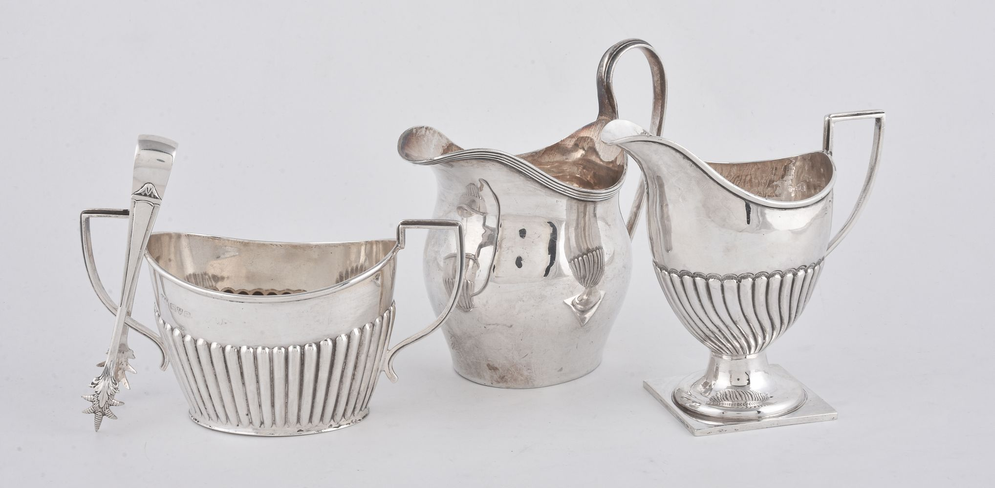 A silver swollen oval cream jug by Nathan & Hayes