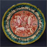 A Persian glazed ceramic plate, decorated with jackals from fables of a Buddhistic source translated