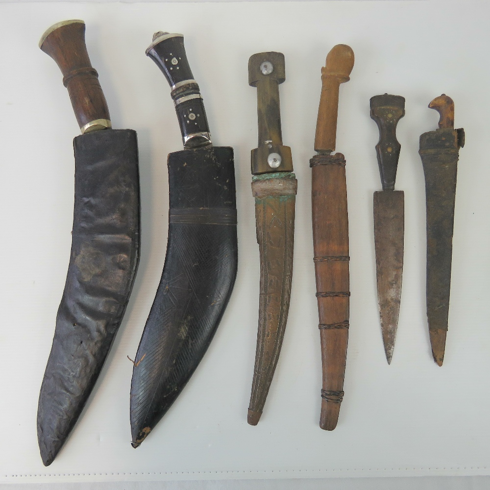 Lot 20 - Two kukris with scabbards, three daggers with sheaths and another without sheath. Six items.