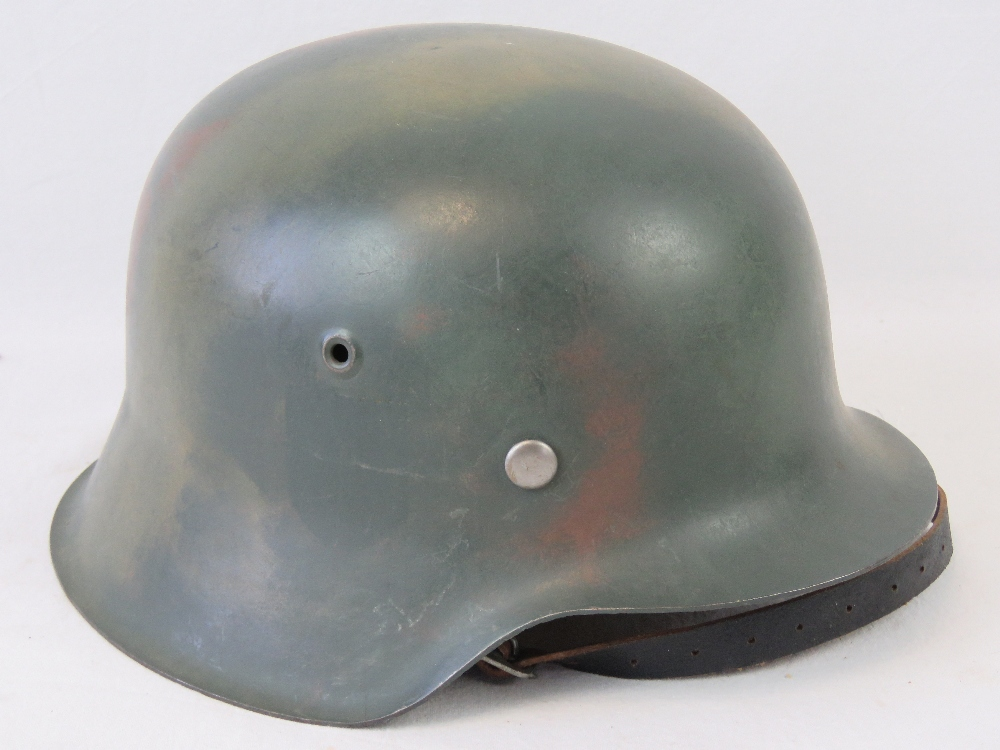 Lot 32 - A good reproduction WWII German Infantry helmet, camo painted with liner and chinstrap.