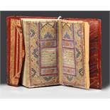 A SMALL RED LEATHER-BOUND QURAN