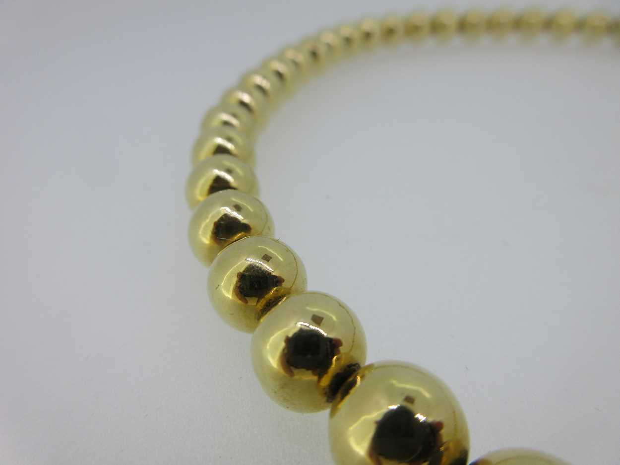 A gold bead necklace stamped '750', in - Cheffins Fine Art