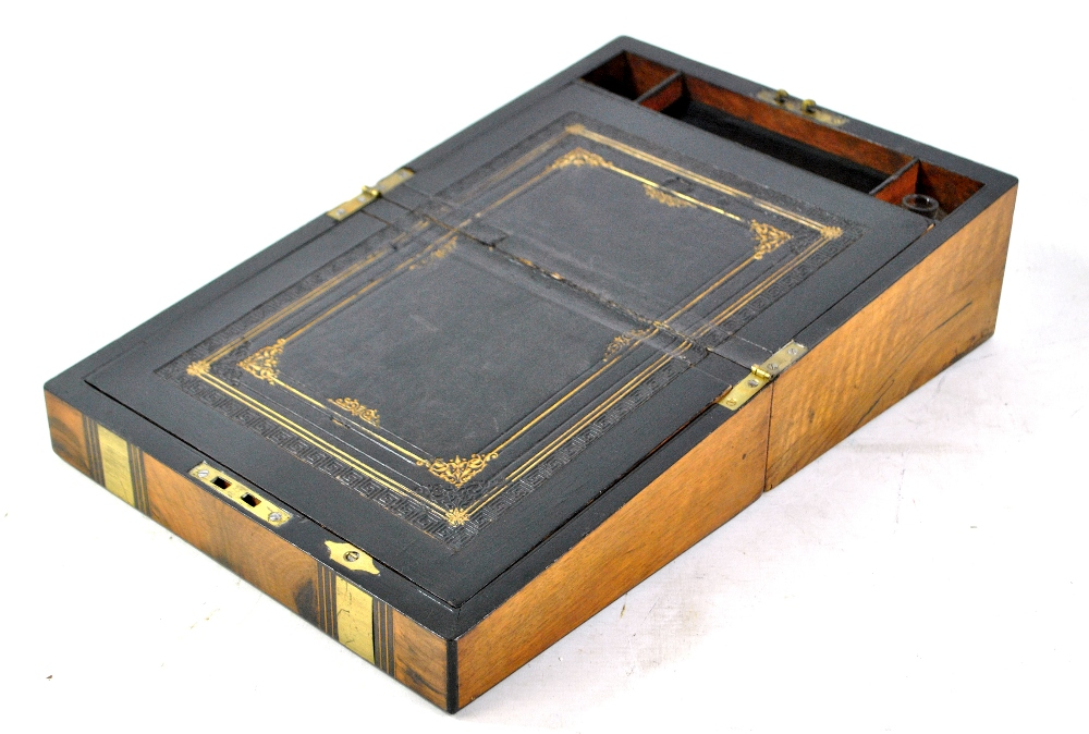 Lot 46 - A Victorian walnut ebony detailed and brass bound writing slope centred with a vacant cartouche,