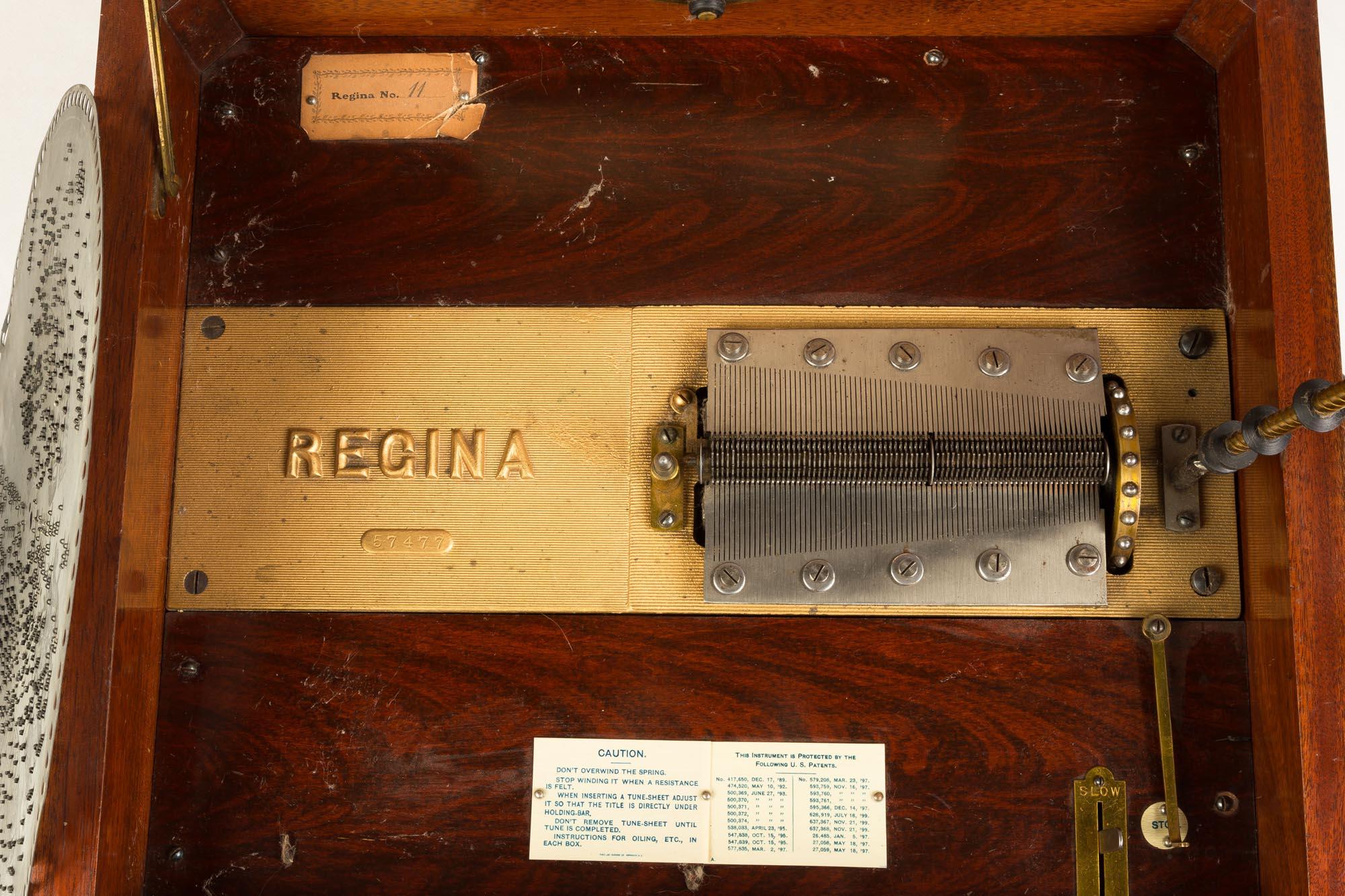 "Lot 218 - Regina Double Comb Music Box. circa 1900. (11) 15 1/2"" disks. Inlaid mahogany case. Working order."