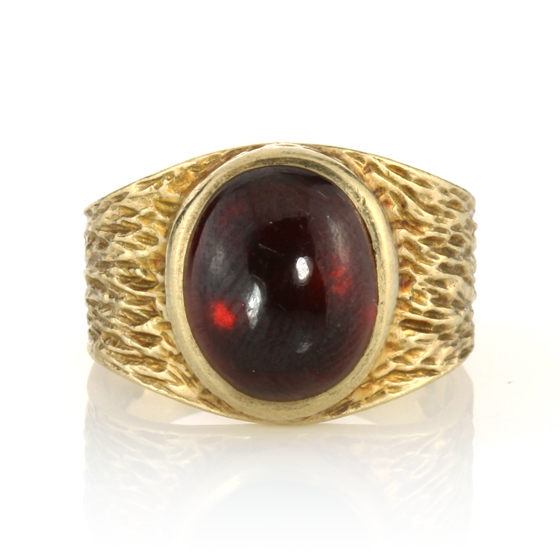 Los 37 - A GARNET DRESS RING, CIRCA 1970 set with a large oval cabochon garnet within a textured band, signed