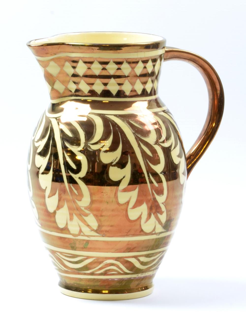 Lot 6 - GORDON FORSYTH (1879-1952); awhite earthenware jug, copper lustre oak leaf decoration on honey