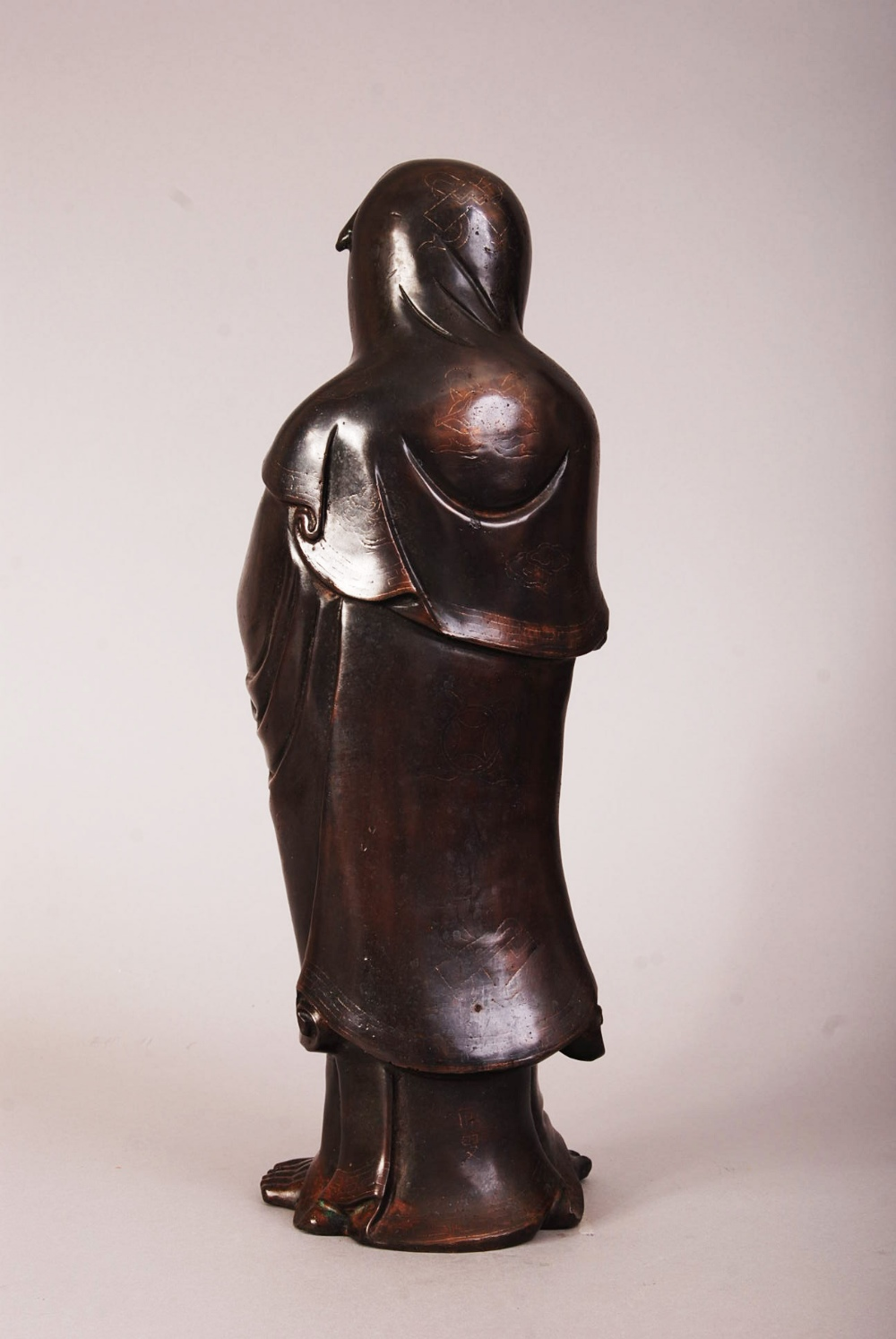 Lot 57 - Chinese silver-inlaid bronze figure of Damo, modelled standing barefoot, wearing loose robes