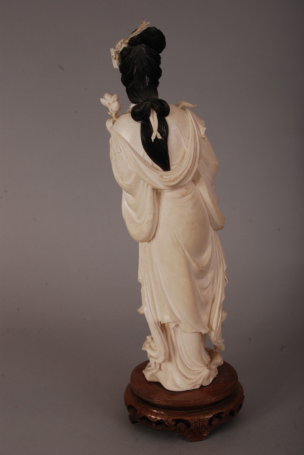Lot 55 - C19th Chinese carved ivory figure of a lady, holding a flower spray and wearing long robes, wood