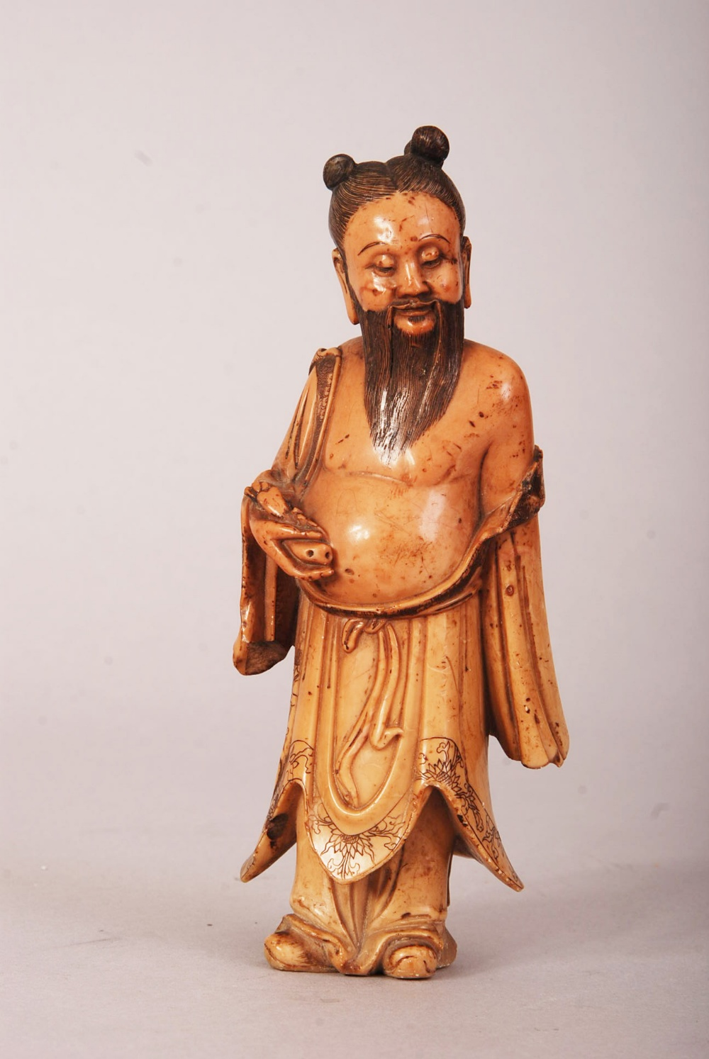 Lot 60 - C17th/18th Chinese carved soapstone figure of an immortal, shown standing and wearing loose robes