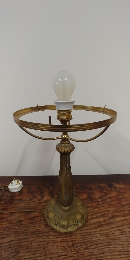 Lot 389 - A solid brass table lamp, the base decorated with floral designs including grapes.