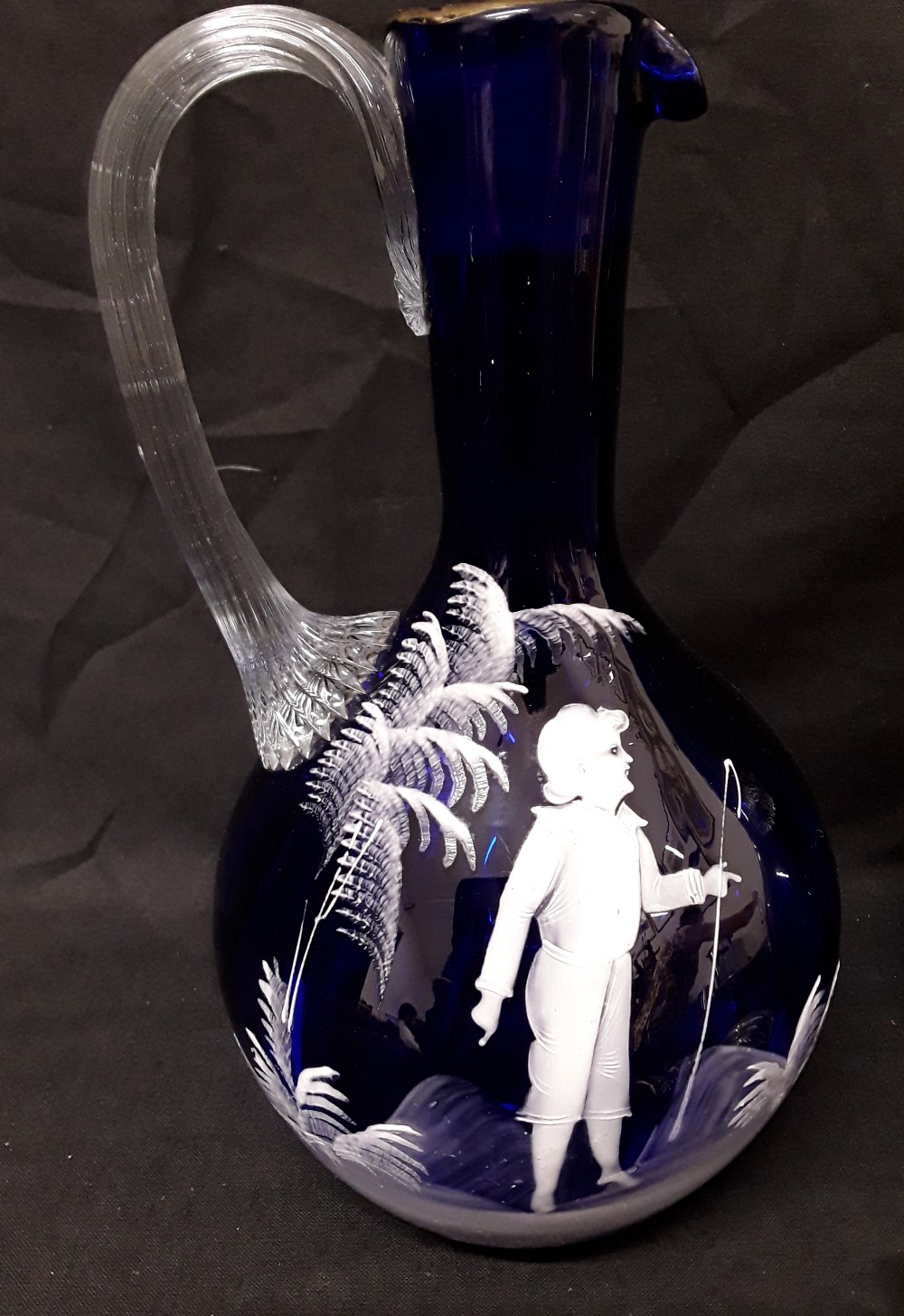 Lot 22 - A pair of Mary Scott hand blown blue glass decanters/water jugs decorated with white enamel figures.