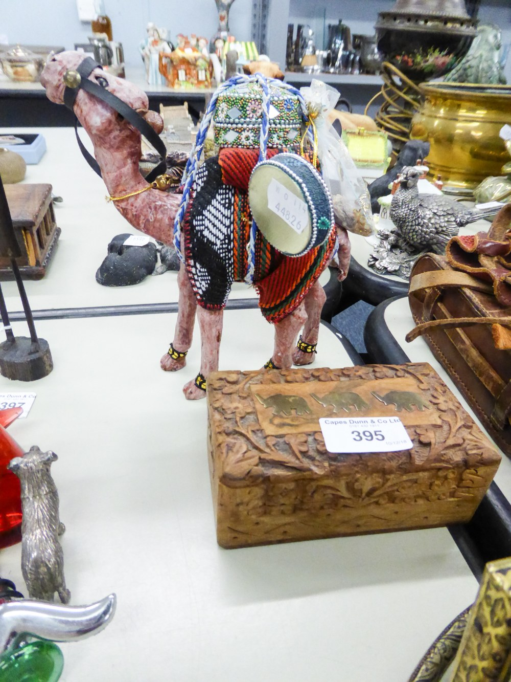 Lot 395 - CARVED WOOD SOUVENIR MODEL OF A CAMEL; FLORAL CARVED TEAKWOOD TABLE CIGARETTE BOX, INLAID WITH BRASS