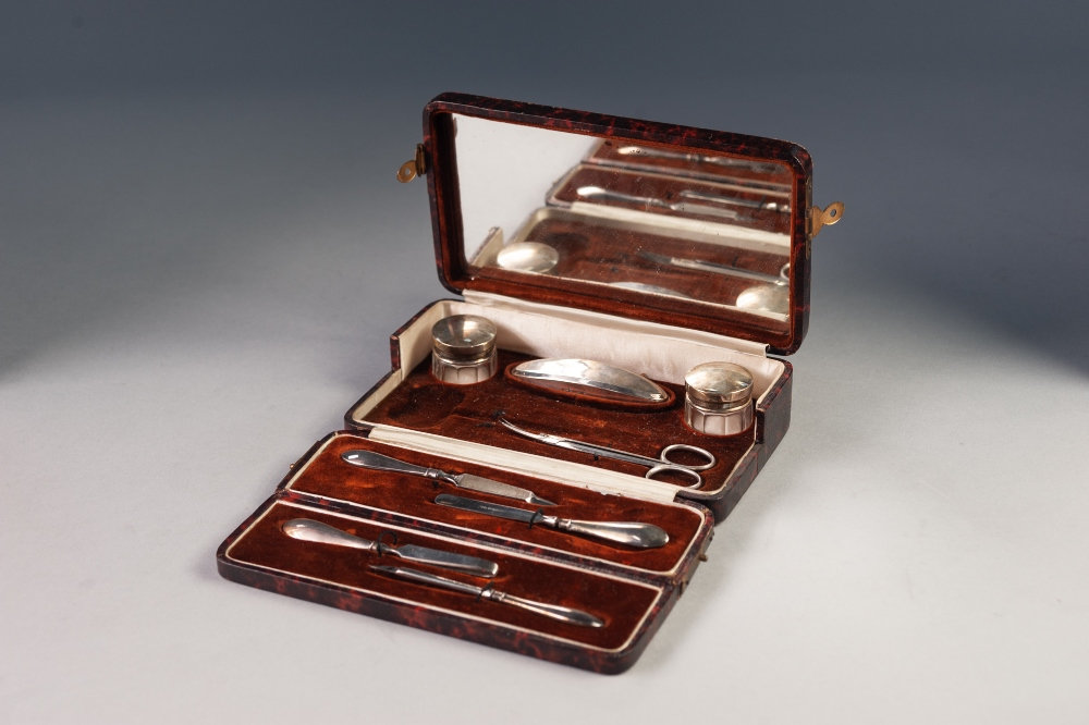 Lot 476 - GEORGE V CASED EIGHT PIECE PART MANICURE SET, comprising; a pair of facet cut small toilet jars with