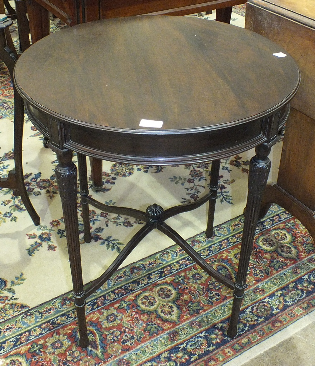 Lot 62 - An Edwardian mahogany circular occasional table on turned and reeded legs joined by stretchers, 61cm