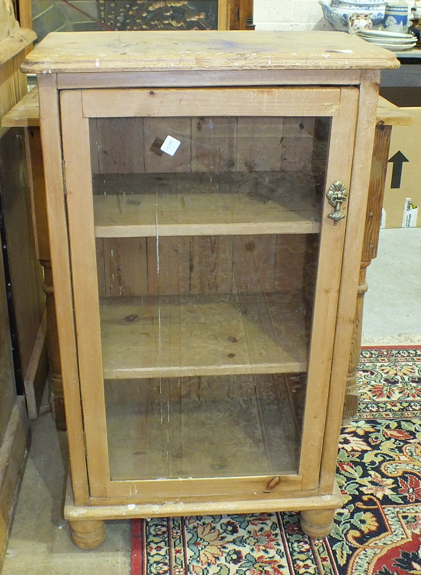 Lot 25 - A stripped pine cupboard with single glazed door, 54cm wide, 94cm high and a pine single-drawer