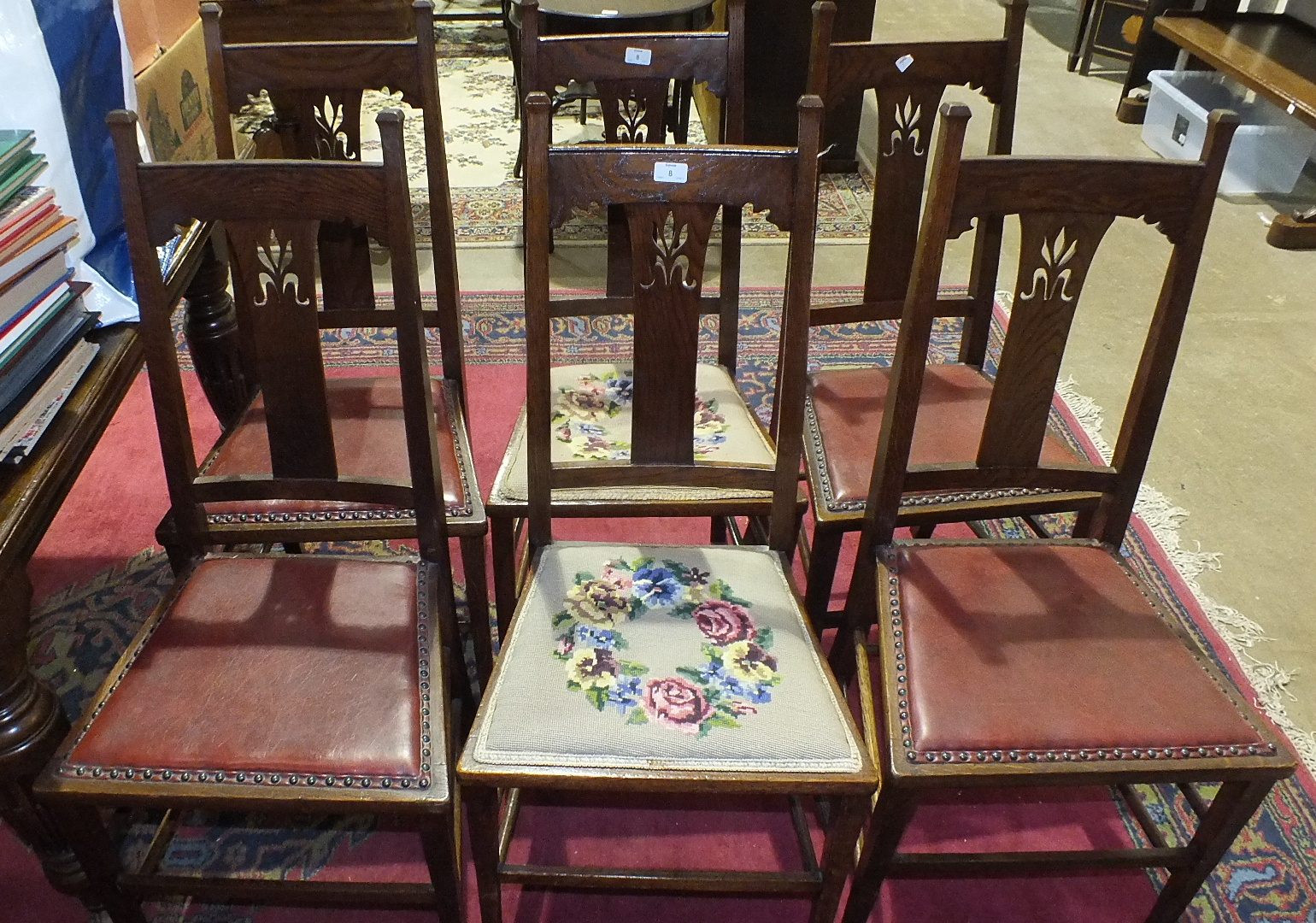 Lot 8 - A set of six oak framed dining chairs with centre splats and padded seats on square tapering front