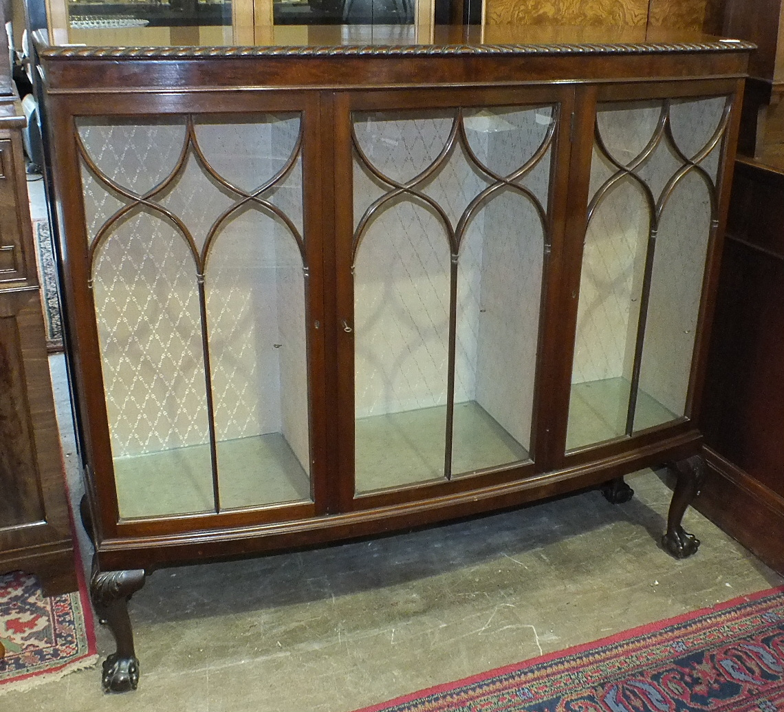 Lot 54 - A mid-20th century mahogany display cabinet, the slightly-bowed rectangular top above three glazed