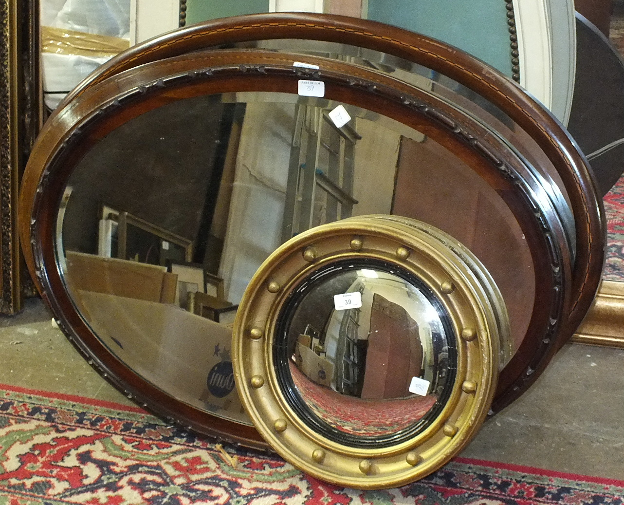 Lot 39 - Two inlaid mahogany oval mirrors, one other and a Regency-style circular convex mirror in gilt