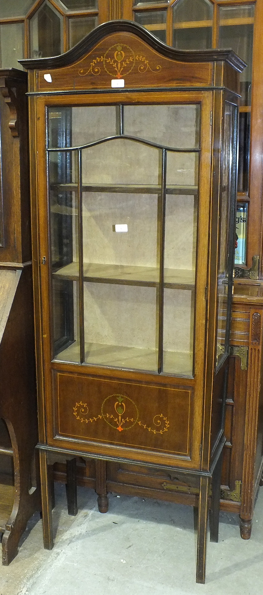 Lot 6 - An Edwardian inlaid mahogany display cabinet fitted with a single glazed door and glazed sides, on