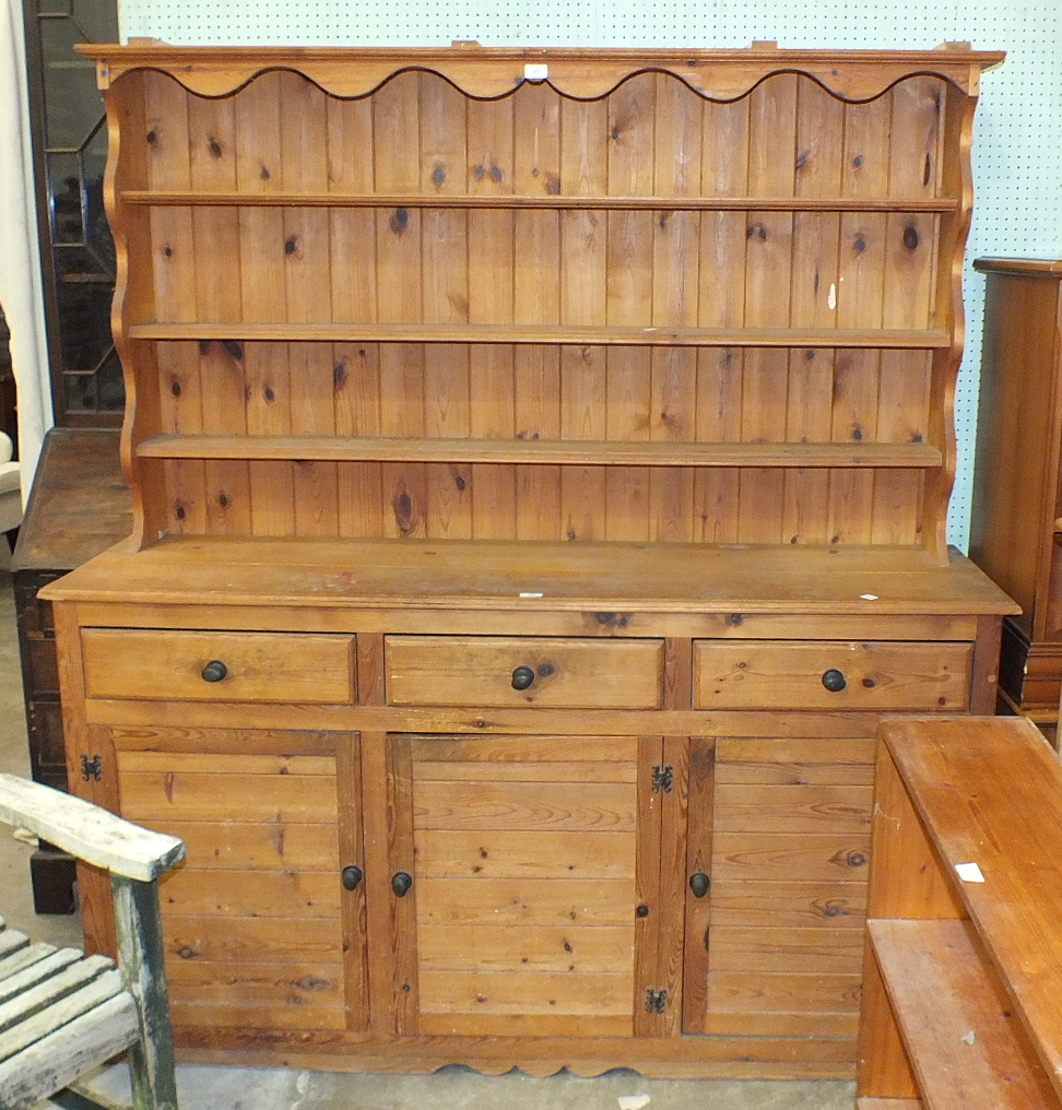 Lot 23 - A modern pine dresser, the open-shelved top above three drawers and three cupboard doors, 167cm