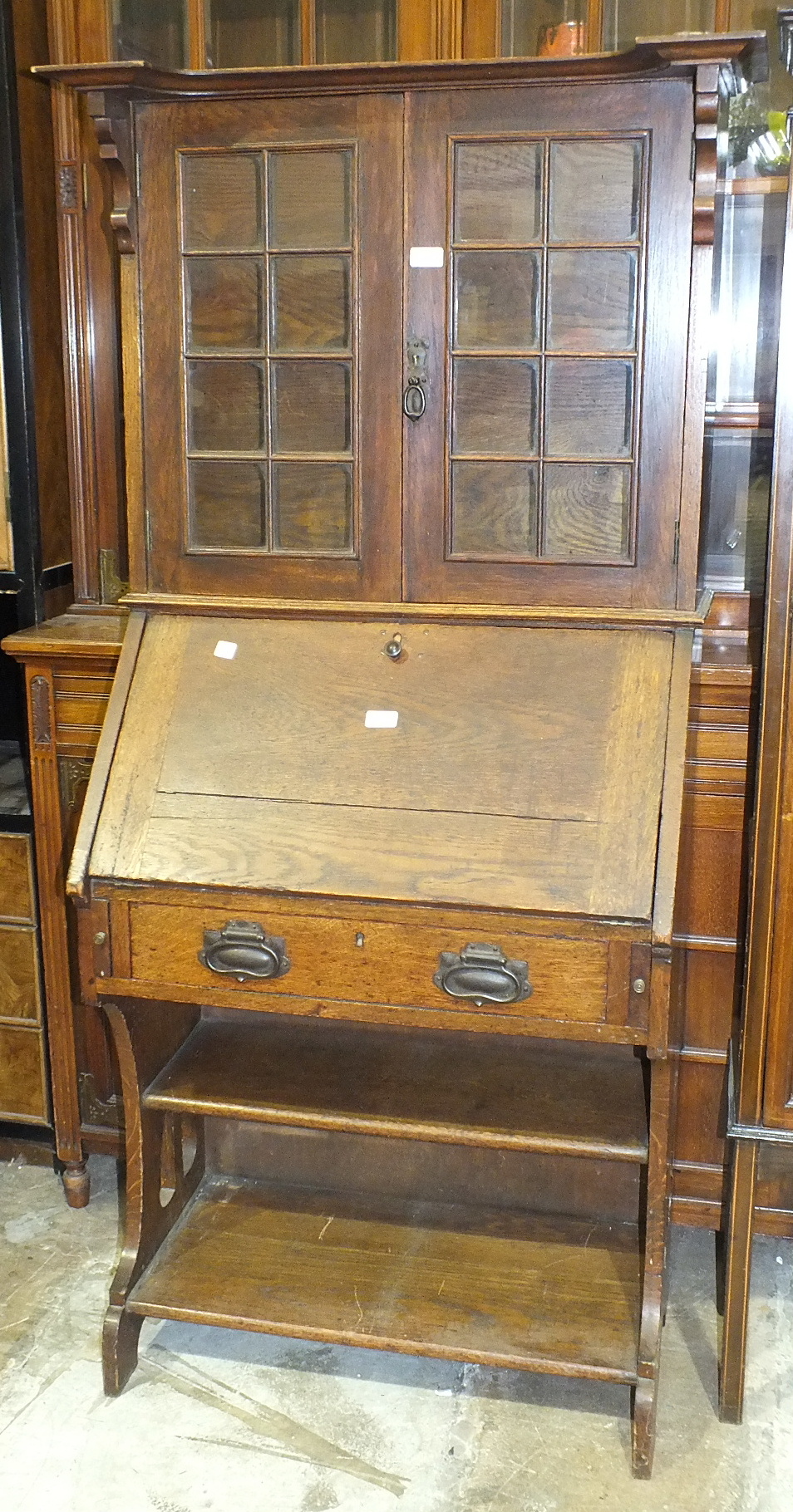 Lot 28 - An Edwardian low oak bureau bookcase, the top fitted with a pair of glazed doors above a fall front,