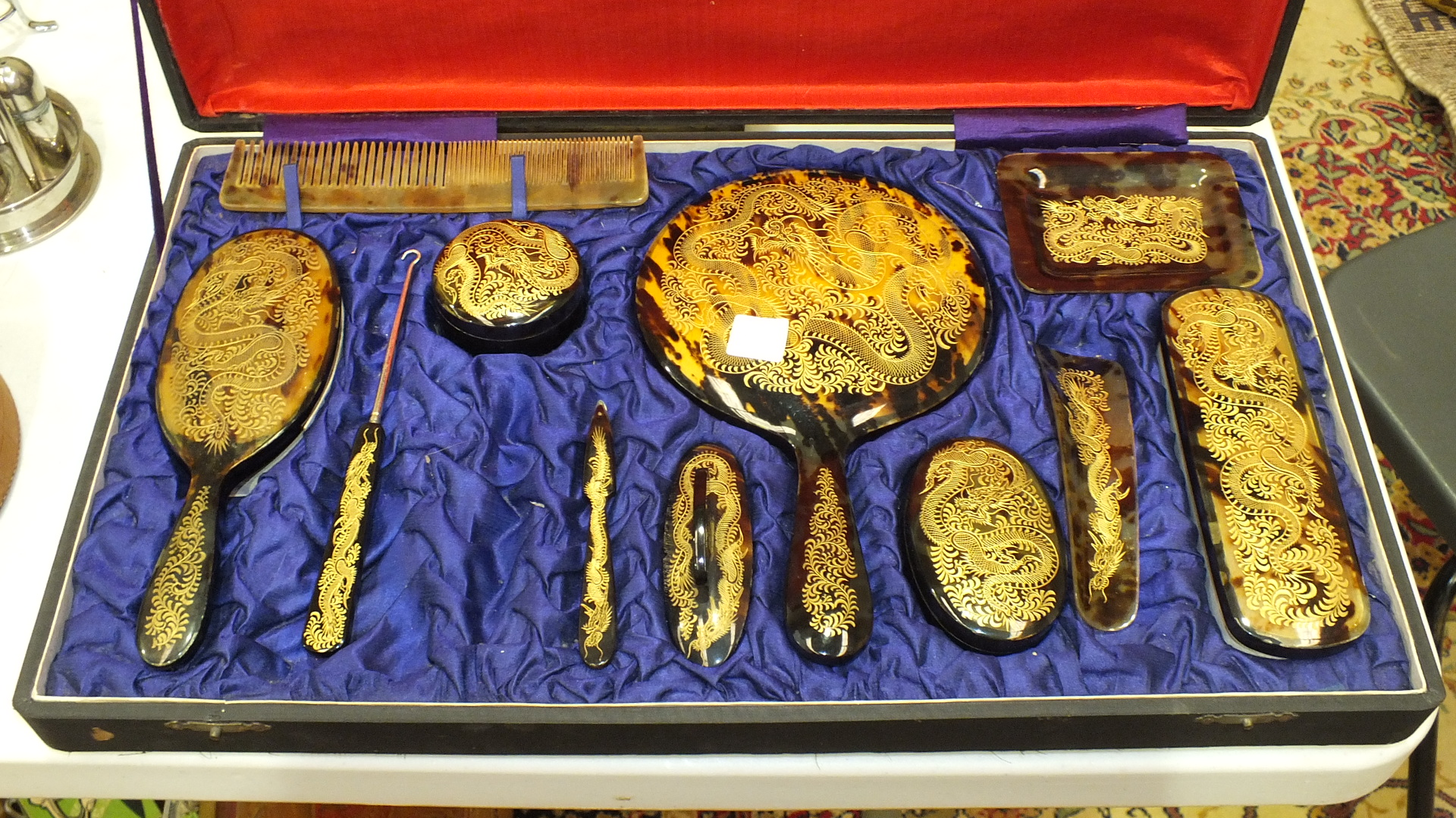 Lot 152 - An early-20th century tortoiseshell part dressing table set inlaid with gilt dragons, in a fitted