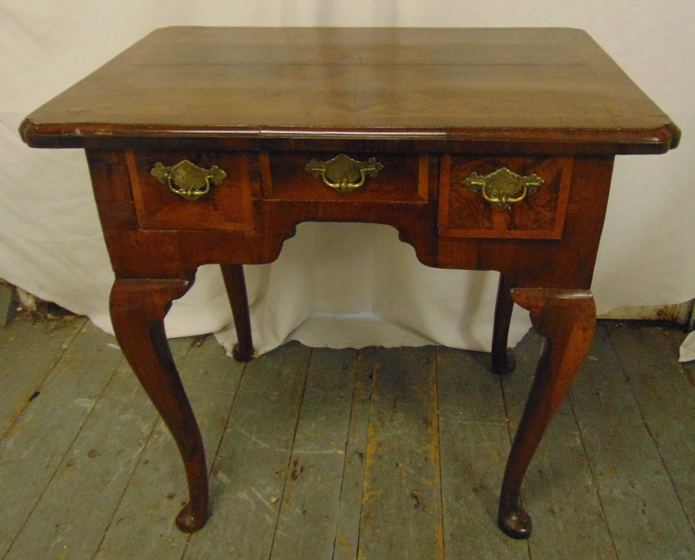 Lot 9 - A Georgian rectangular walnut lowboy with three cross banded drawers, four cabriole legs with pad