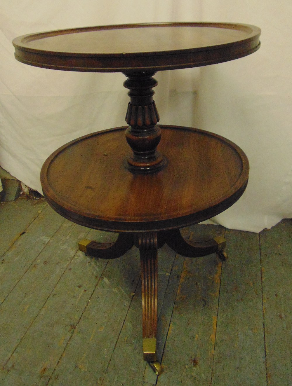 Lot 28 - A 19th century circular mahogany two tier dumb waiter trolley on tripod feet with brass caps and
