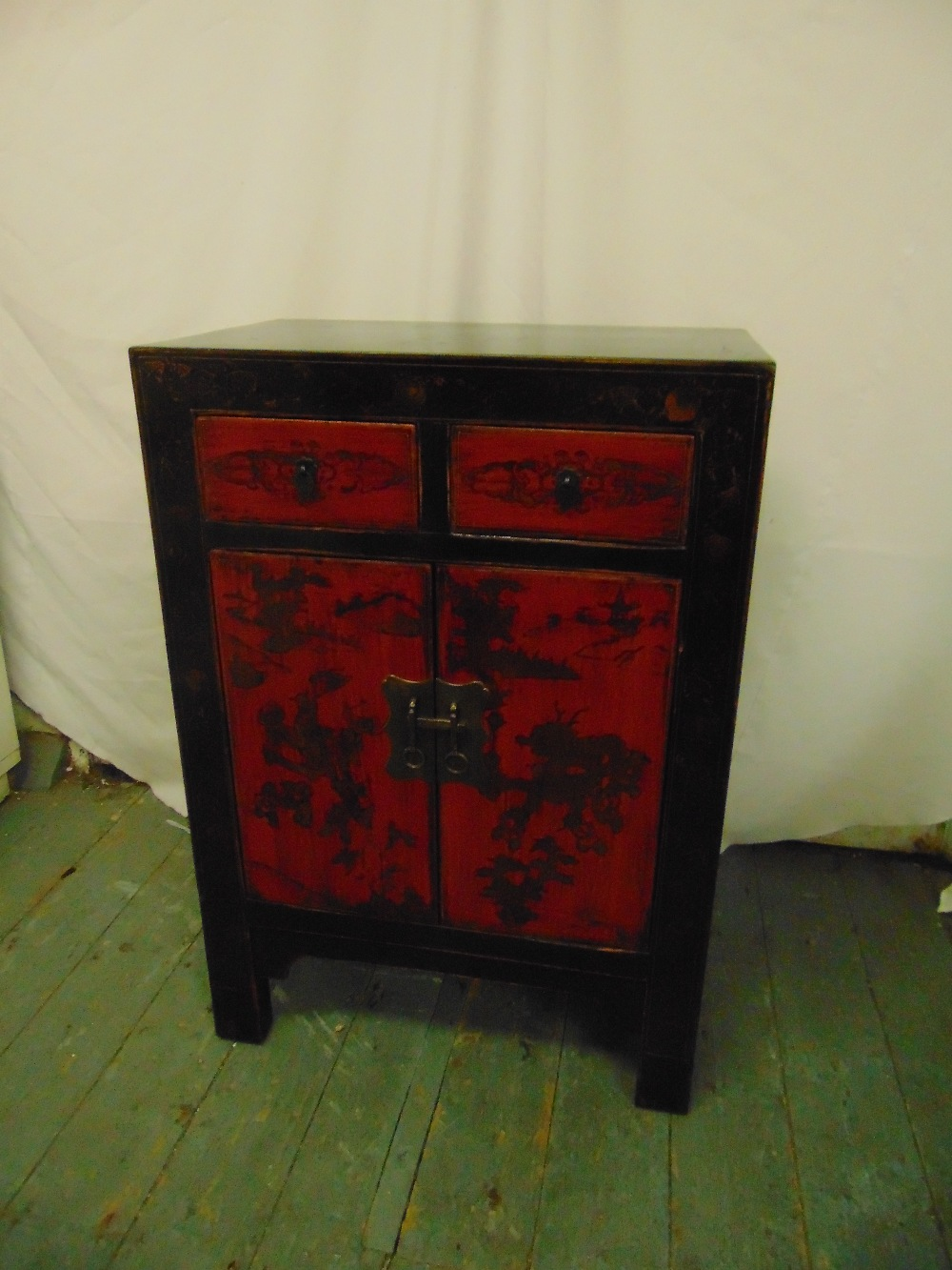 Lot 22 - An Oriental rectangular lacquered cabinet with two drawers and hinged doors