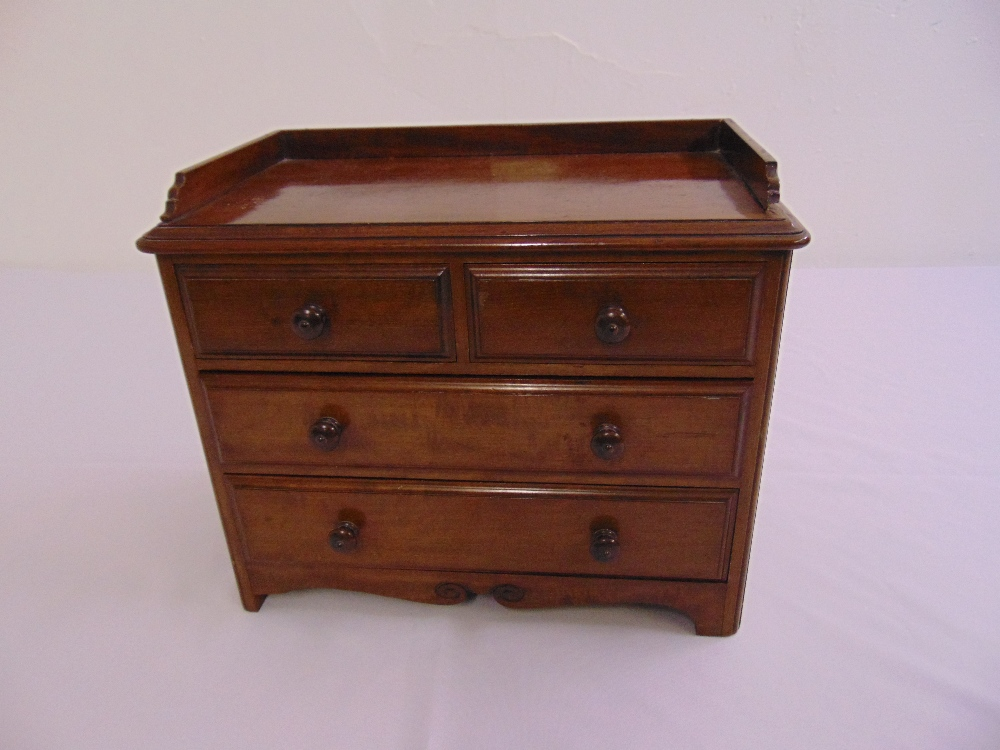 Lot 51 - A rectangular mahogany table-top apprentice chest of drawers with turned wooden handles