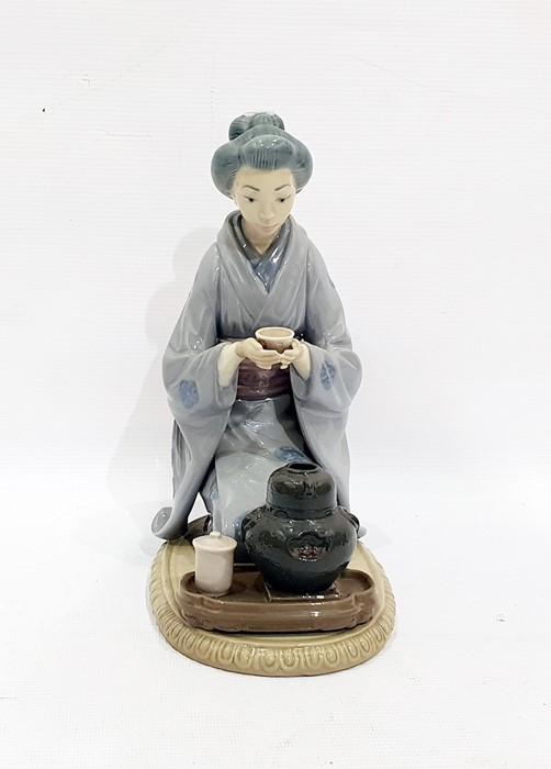 Lot 48 - Two Lladro figures of geishas, one kneeling at a tea ceremony and another kneeling arranging flowers