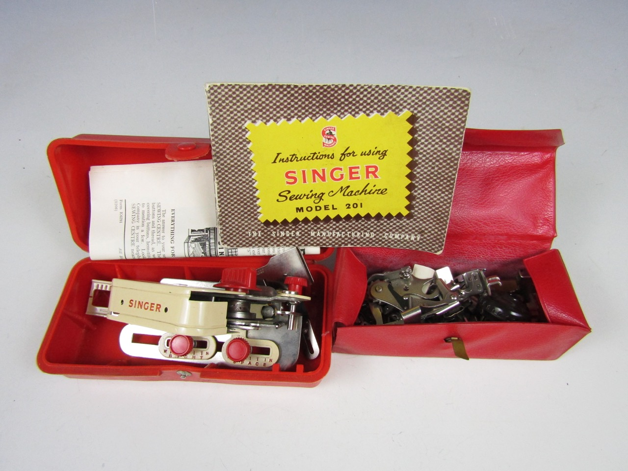 Lot 26 - A vintage cased Singer buttonhole attachment implement together with Singer attachments and