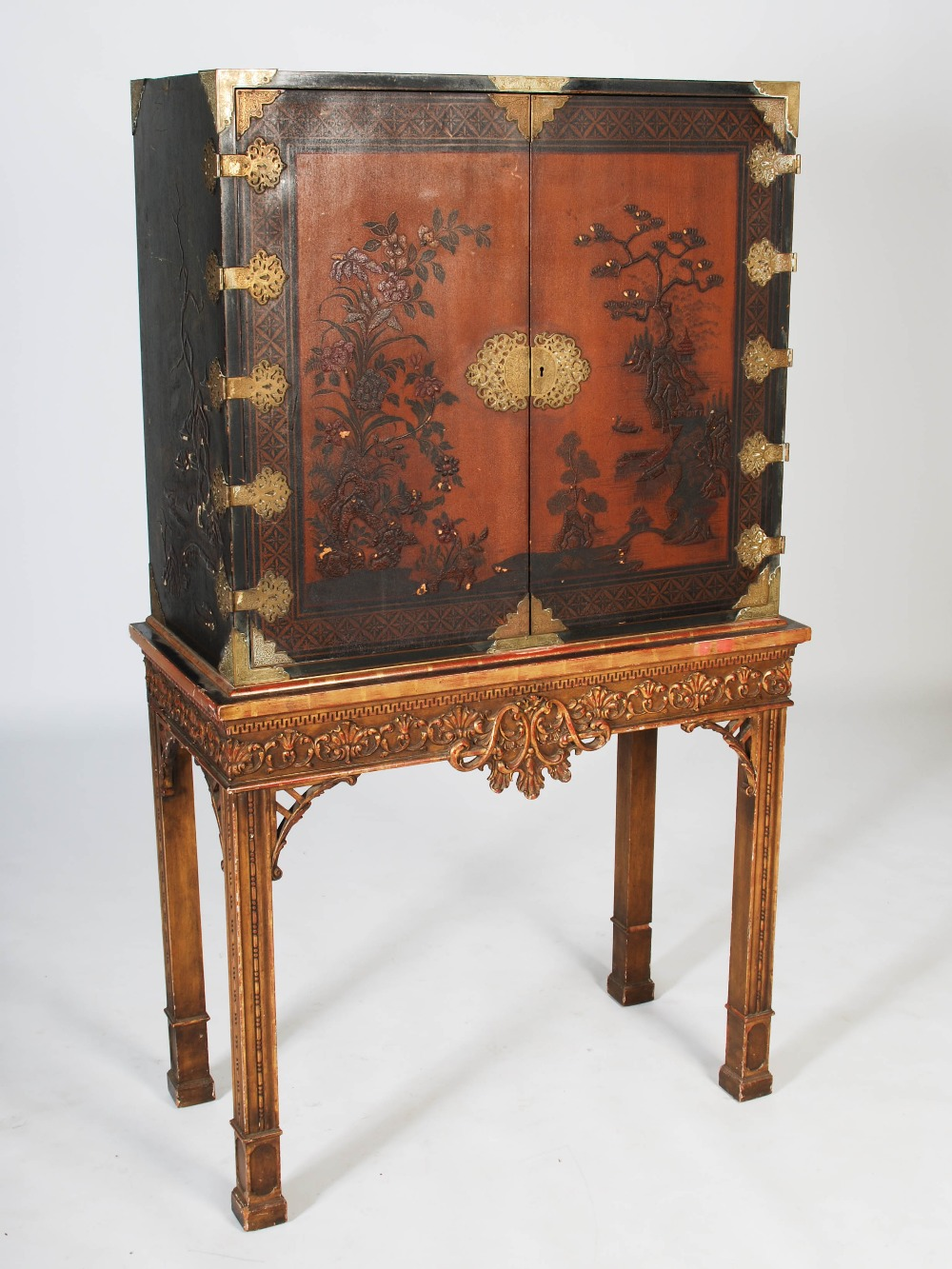 Lot 107 - An early 20th century chinoiserie decorated lacquered cabinet on stand, the cabinet with a pair of