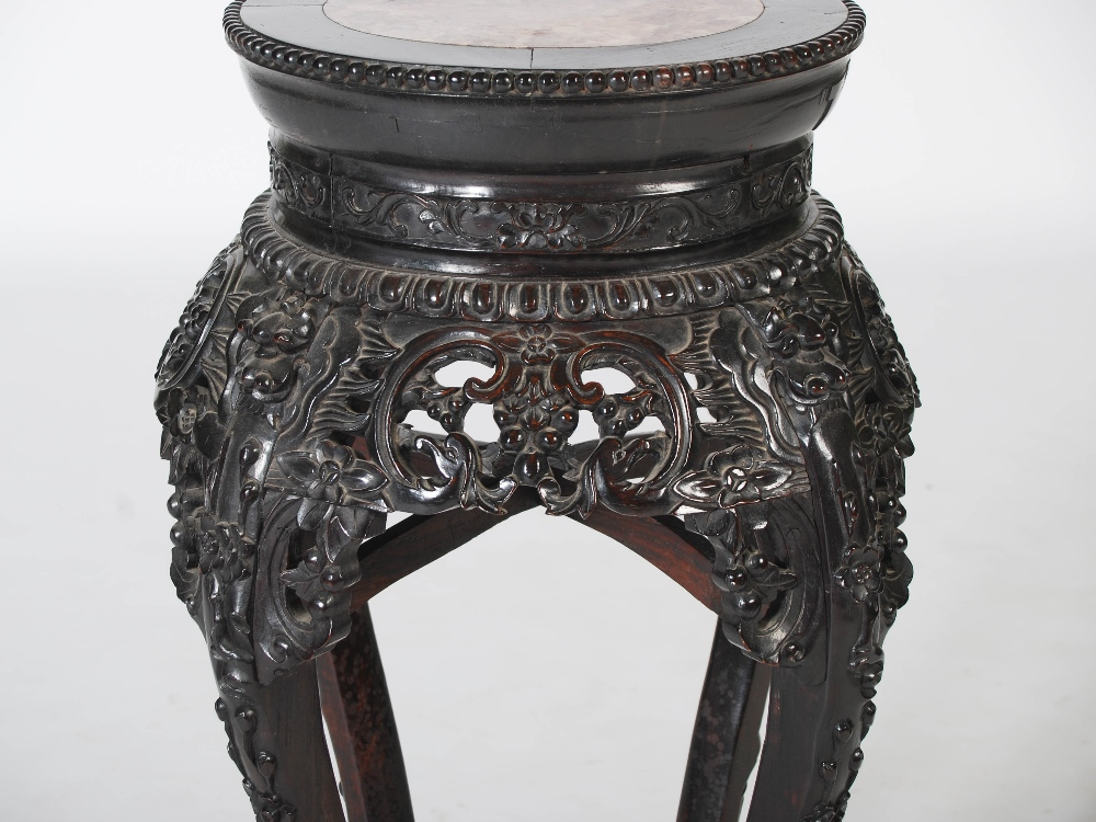 Lot 42 - A Chinese dark wood jardiniere stand, Qing Dynasty, the circular top with a mottled red and white