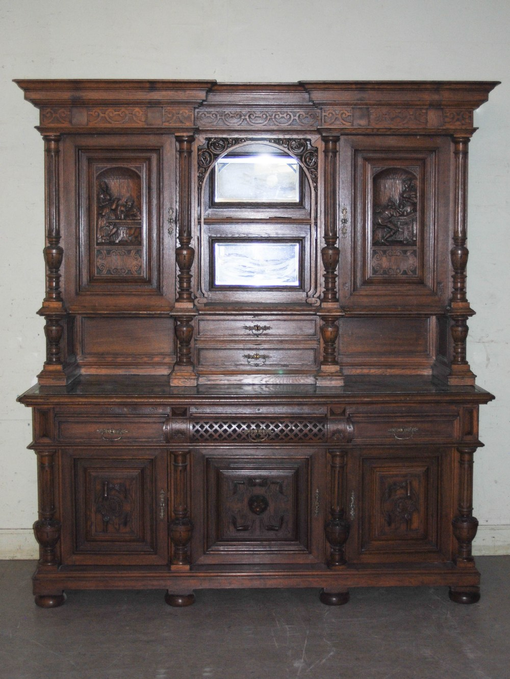 Lot 97 - A late 19th century oak sideboard, the upright back with two bevelled mirror recesses and two