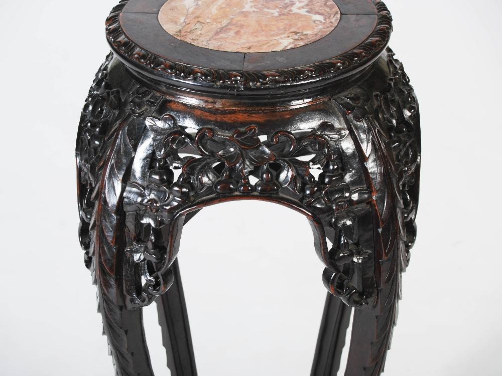 Lot 26 - A Chinese dark wood jardiniere stand, Qing Dynasty, the circular top with mottled red marble insert,