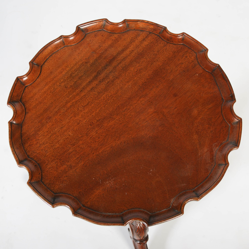 Lot 47 - A George III style mahogany tripod occasional table, the circular top with pie crust edge, raised on