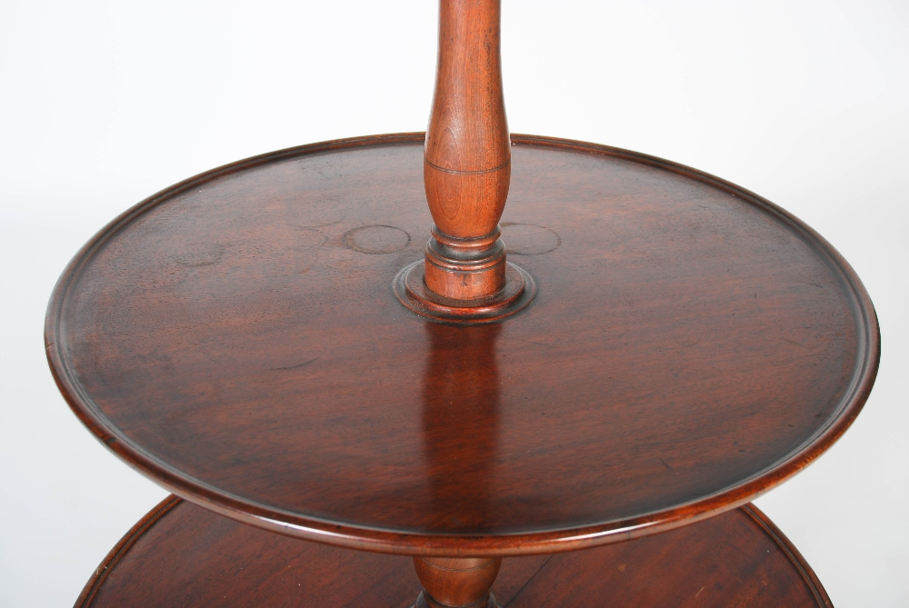 Lot 13 - A George III mahogany three tier revolving dumb waiter, the graduated revolving stand supported on