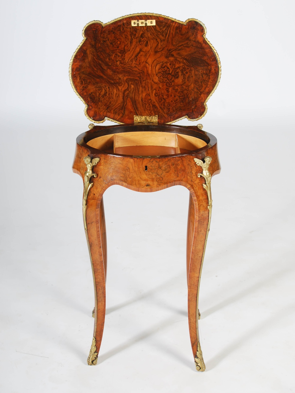 Lot 67 - A late 19th century walnut and ormolu mounted work table, the hinged oval top opening to a fitted