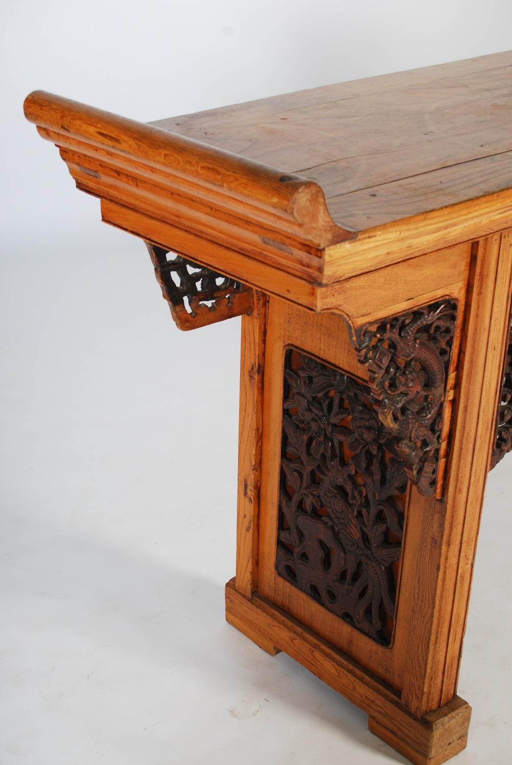 Lot 109 - A Chinese elm wood altar table, the rectangular top with scroll carved ends, raised on two