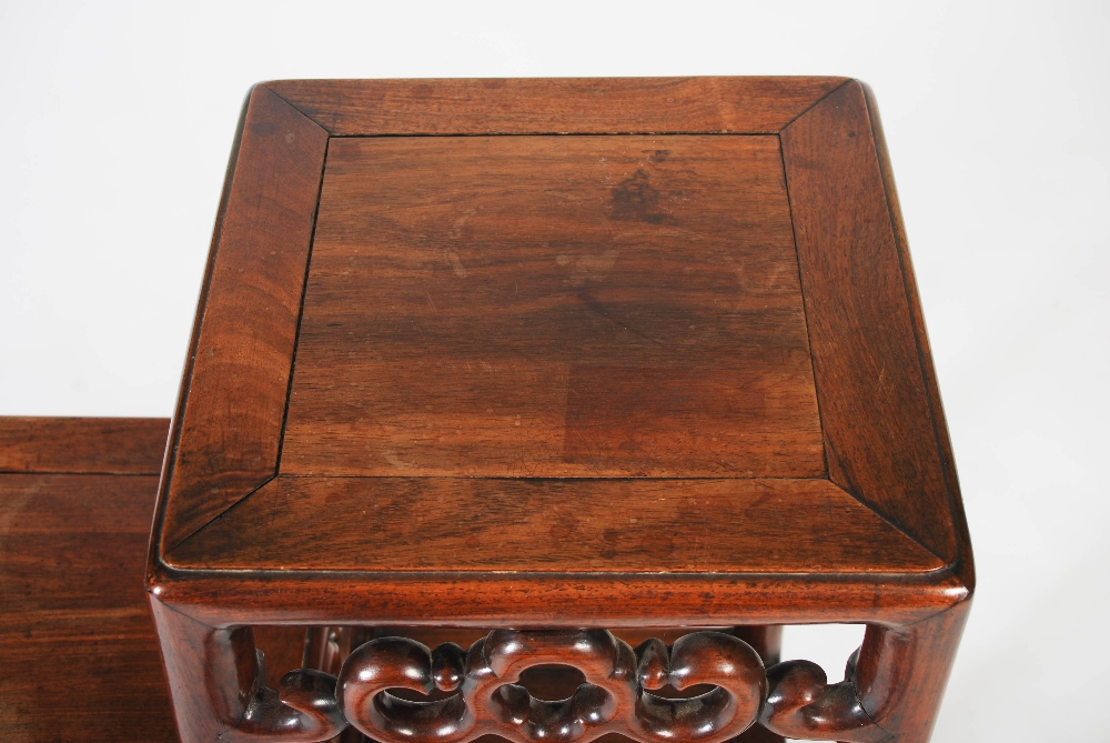 Lot 54 - A Chinese dark wood stand, Qing Dynasty, of asymmetric rectangular form, raised on cylindrical