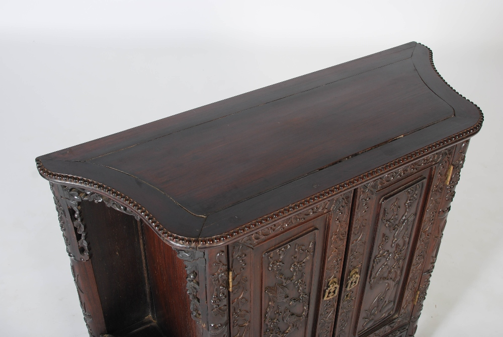 Lot 86 - A Chinese dark wood side cabinet, the shaped panel top above a pair of panelled cupboard doors